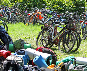 parked bicycles and many backpacks on the lawn during a stop in