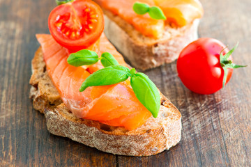 Salmon sandwich on wooden table with tomato