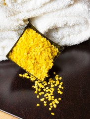 Spa massage with towel stacked and yellow sea salt