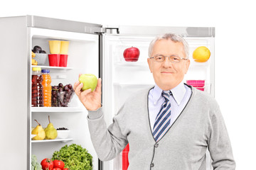 Senior man taking apple out of the refrigerator