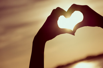 Love sign. Heart symbol by hand silhouette in sunset sky. Vintag