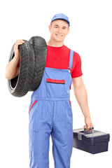 Male mechanic carrying tires and holding toolbox