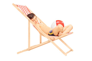 Cute little boy sleeping in a sun lounger