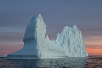 Iceberg in Antarctic waters at sunset autumn day