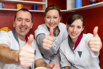 Drei Ärzte mit Daumen hoch lächeln zum Betrachter