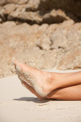 women's feet in the sand