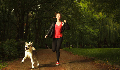 Teenage girl running in park with dog