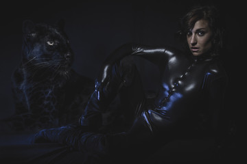 Sensual brunette woman dressed in latex with huge black panther