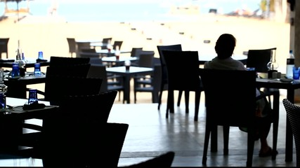 girl or womаn enjoying ocean or sea vew at the restaurant table