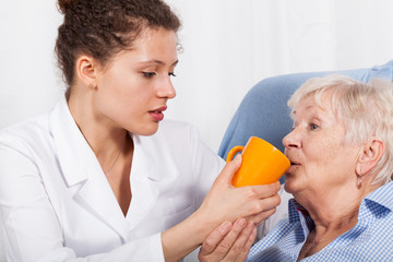 Nurse gives drinking old woman