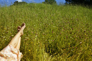 Barefoot of young girl lying on meadow