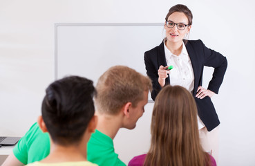 Young teacher pointing on talking student