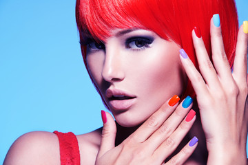 Portrait  of a model with red hairs and multicolor nails.
