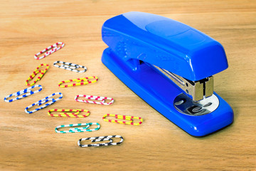 Stapler of bright blue color and paper clip against a table.
