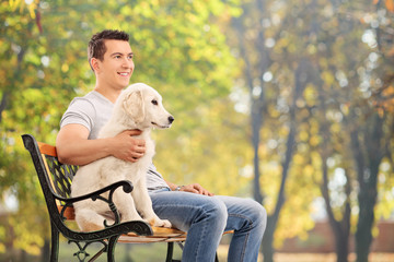 Man sitting on bench with a young dog