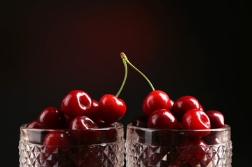 Sweet cherries in glasses on dark background