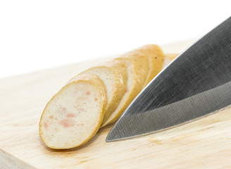 Sausage with knife over cutting board