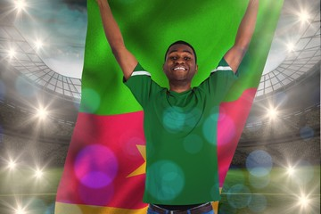 Composite image of cheering football fan in green jersey holding