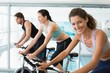 Fit people in a spin class with woman smiling at camera
