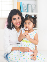 indian mother enjoying ice cream with her daughter on lifestyle