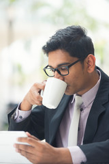 young indian business man with a tablet computer and coffee at a