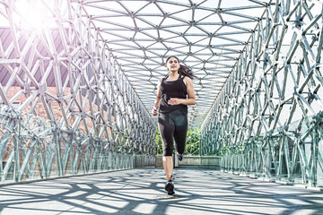 Abstract - Beautiful woman running on a modern metal bridge