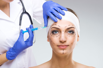 Beautiful woman with plastic surgery, holding a needle