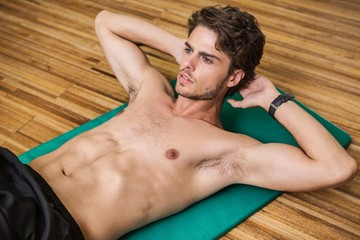 Fit shirtless man doing sit ups in fitness studio