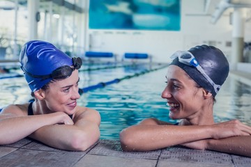 Female swimmers smiling at each other in the swimming pool