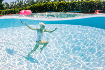Woman having fun underwater with red heart balloon in swimming p