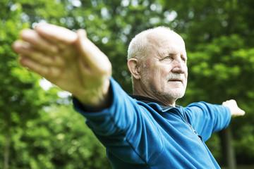 senior macht gymnastische übungen,sport, im park