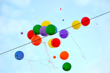 festival is over.. multicolored balloons catch on electric cable