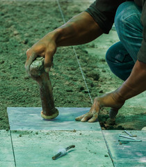 Construction man worker floor tile installation with hammer.