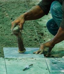 Construction man worker floor tile installation with hammer.