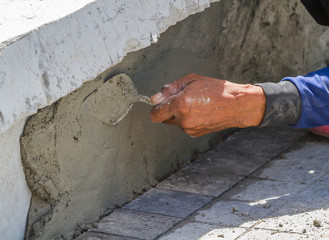 Man working wall for cement with trowel.