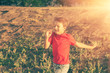 Blurred motion of a boy  running against sun