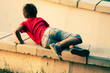 Boy playing on a cemet parapet