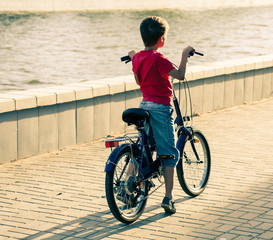 Backside view of a boy on bike near water