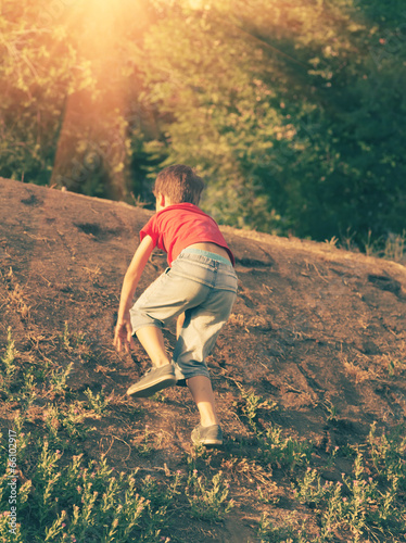 Boy climbing up the slope backlit