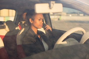 Young black businesswoman fastening seat belt in car
