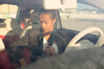 Young businesswoman fastening seat belt in car