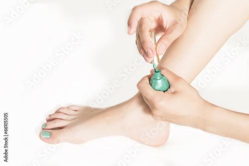 teenage girl paints her toenails