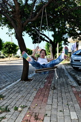 A girl riding a swing and screams