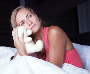 a young girl is sad in bed with a toy