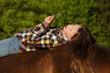 Jugendliche mit Pusteblume auf Pferderücken