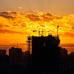 Silhouette of the tower crane on the construction site