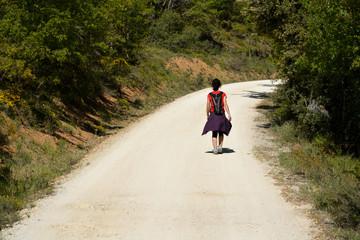 mujer subiendo por un camino en verano