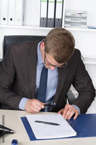 canvas print picture Junger Mann benutzt eine Lupe