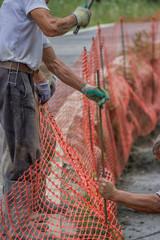 Construction workers set orange safety fence