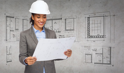 businesswoman in white helmet with blueprint